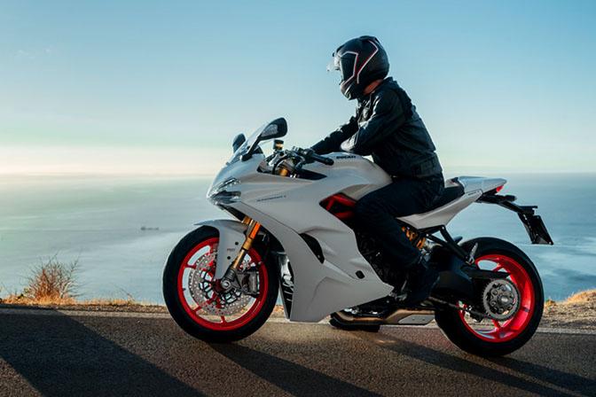 Vista lateral de piloto parado en la Ducati SuperSport frente al mar